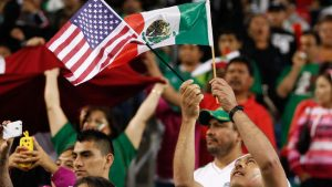 A Mexico fan holds up the flags of traditional soccer rivals at CenturyLink Field in 2013. Photo by Getty Images